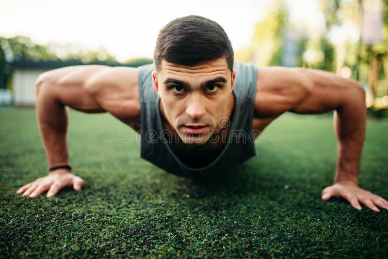 Athlète masculin faisant l'exercice de pompe extérieur photo stock