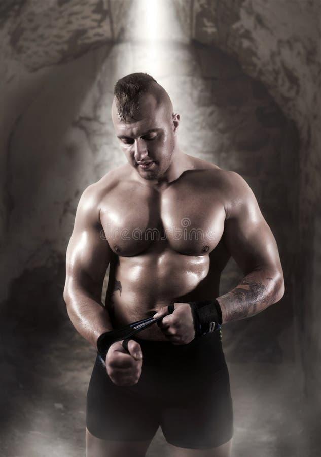 Athlète masculin musculaire posant dans le gymnase images stock