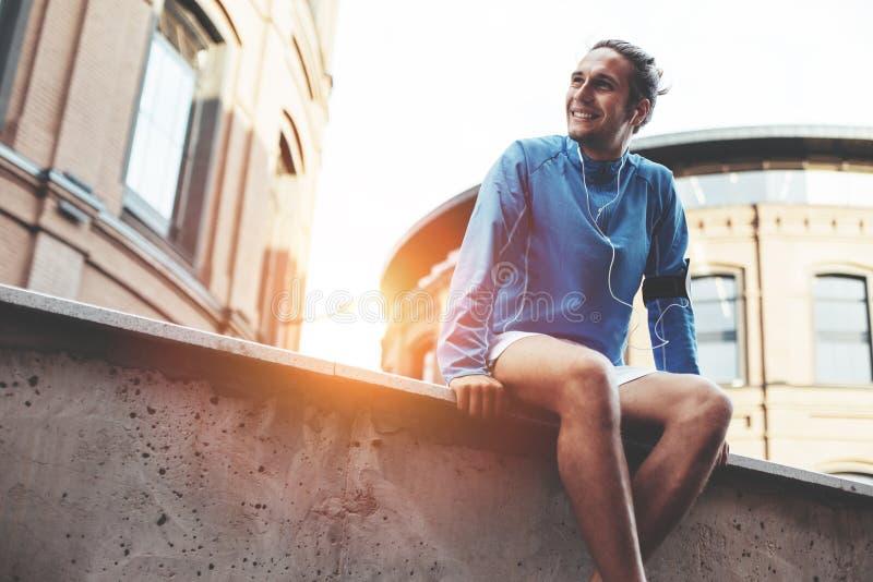 Athlète masculin s'asseyant et se reposant après session de séance d'entraînement de rue photographie stock libre de droits