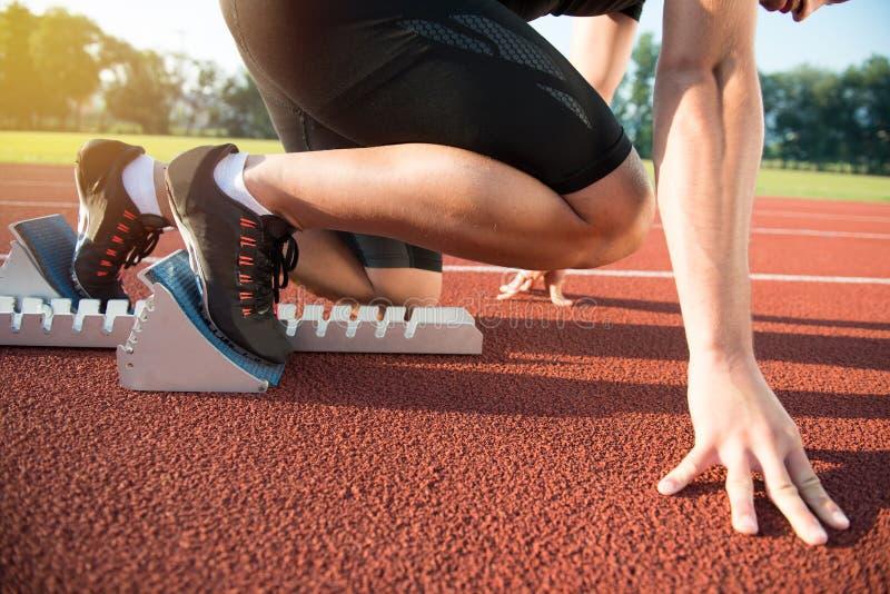 Athlète masculin sur la position de départ à la voie courante d'athlétisme images stock