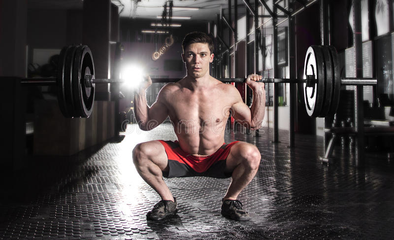 Athlète musculaire attirant de crossfit faisant l'exercice accroupi dans le MOIS photographie stock libre de droits