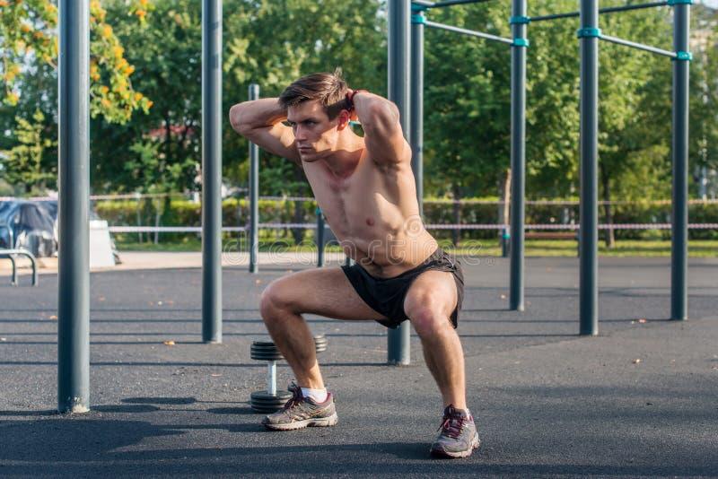 Athlète musculaire de forme physique faisant des postures accroupies avec ses mains derrière le chef s'exerçant en parc photo libre de droits