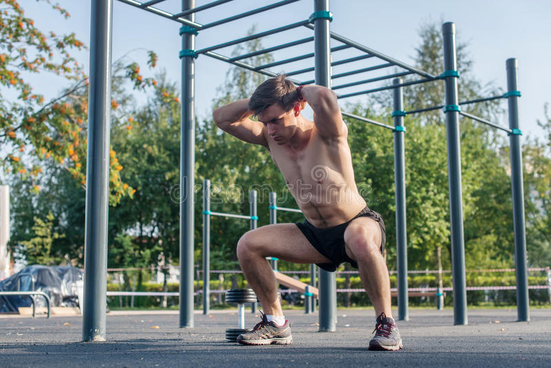 Athlète musculaire de forme physique faisant des postures accroupies avec ses mains derrière le chef s'exerçant en parc photo stock