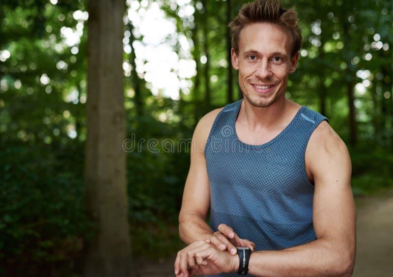 Athlète musculaire réglant son chronomètre photos libres de droits