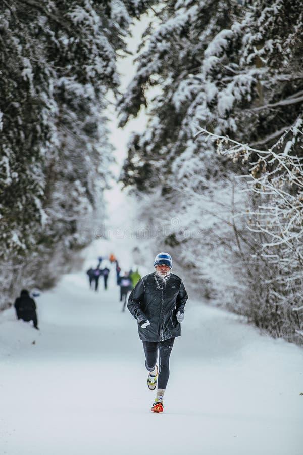 Athlète plus âgé courant en bois d'hiver en temps froid d'allée dans la forêt photos stock