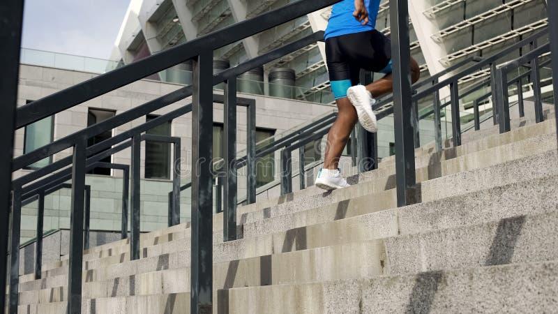 Athlète réchauffant avant la concurrence, fonctionnant en haut près de la vie d'active de stade images stock