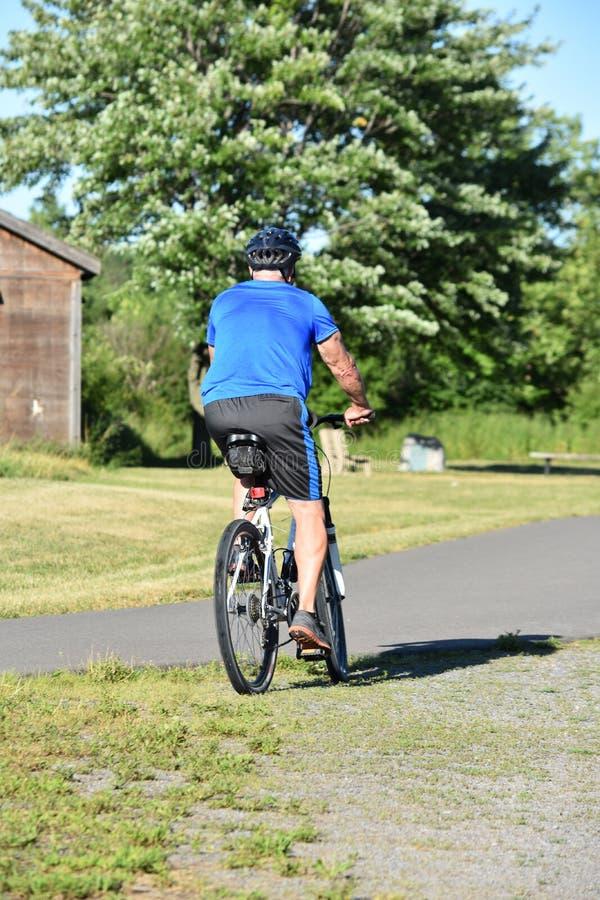 Athlète Retiree Male Cyclist et faire du vélo d'exercice photos stock