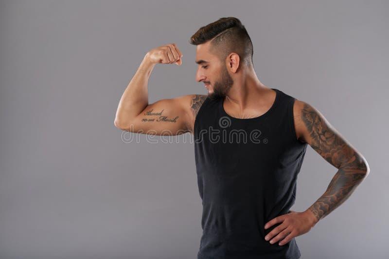 Athlète sûr montrant le muscle de biceps photographie stock libre de droits