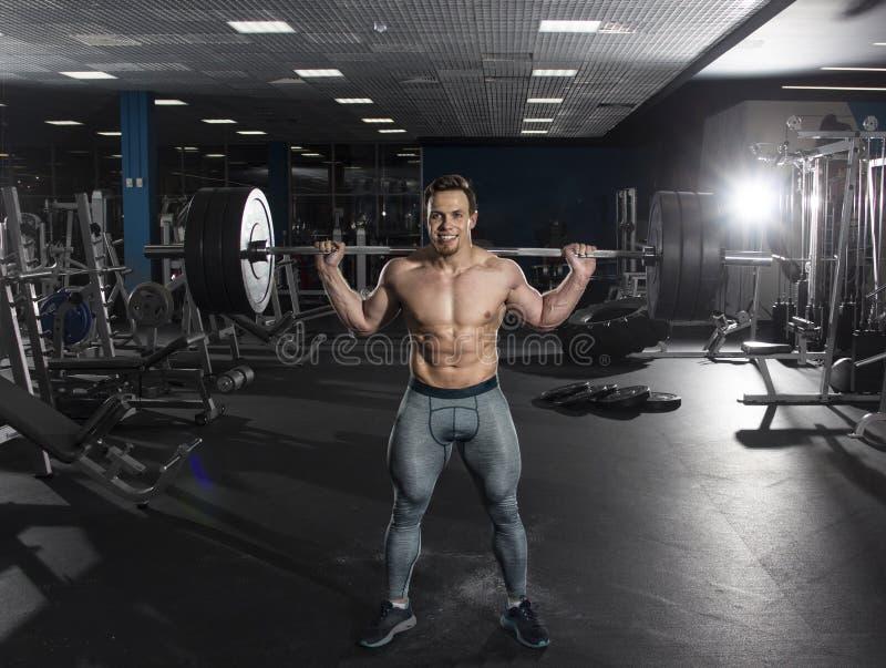Athlète sans chemise musculaire attirant faisant des exercis accroupis lourds photographie stock