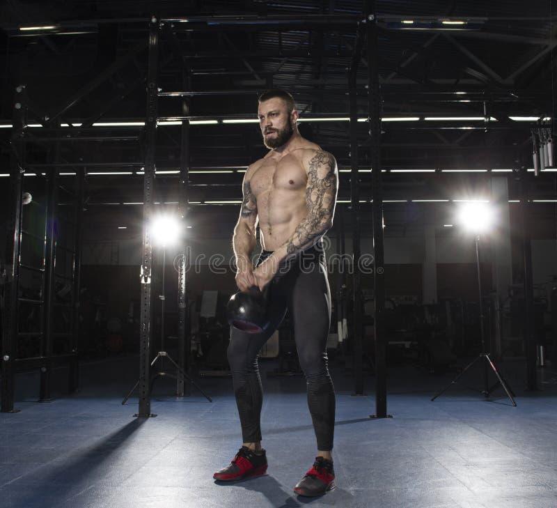 Athlète sans chemise musculaire faisant des oscillations de kettlebell TR fonctionnel images stock
