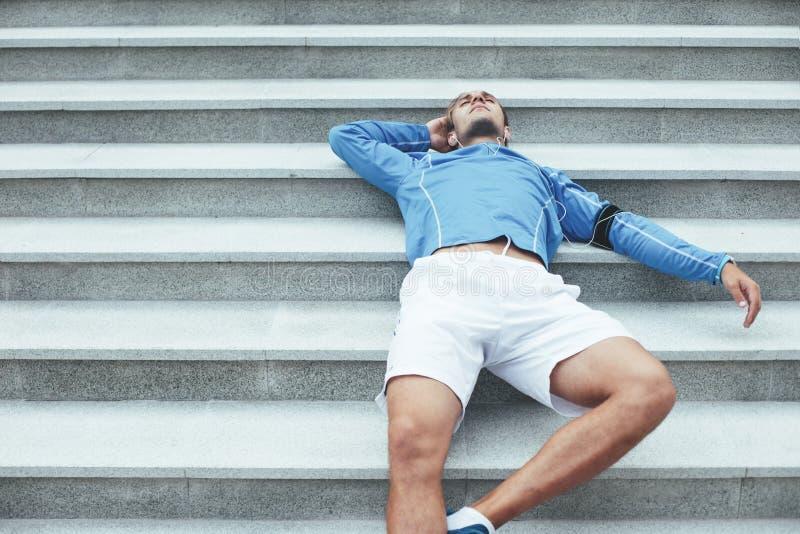 Athlète se reposant sur les escaliers après séance d'entraînement, le brassard avec le téléphone et les écouteurs avec la musique images stock