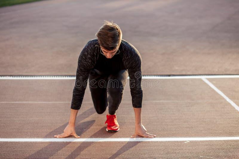 Athlète sur la position de départ à la voie courante Pratique en matière de coureur courue dans le champ de courses de stade photographie stock