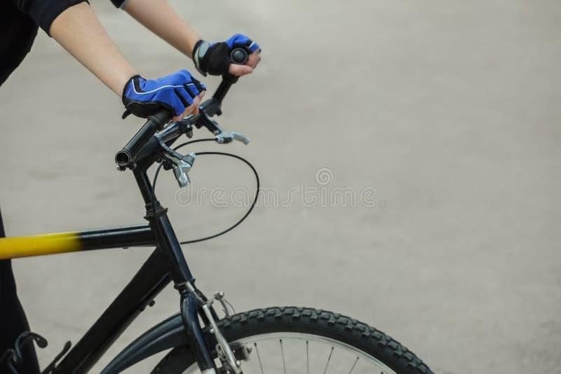 Athlète tenant le guidon de mains Dans les mains dessus mis des gants bleus cycle photo stock