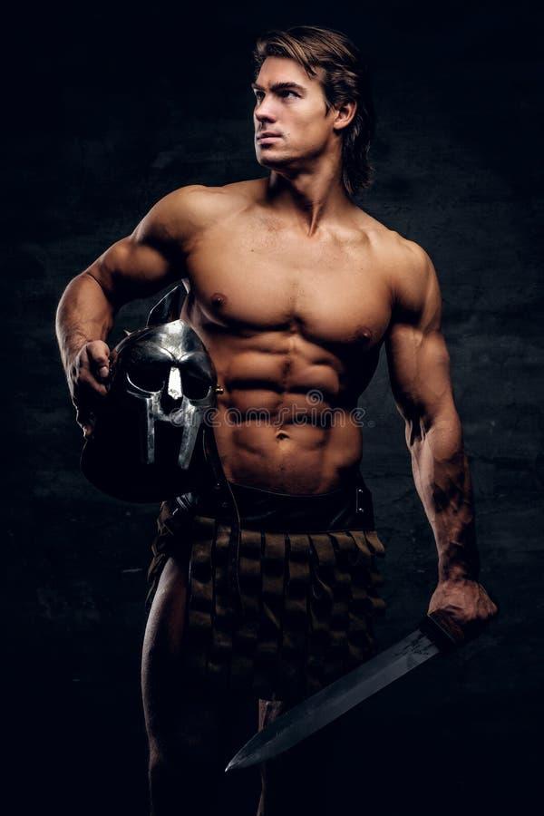Athlète viril avec l'épée et casque dans des ses mains images stock