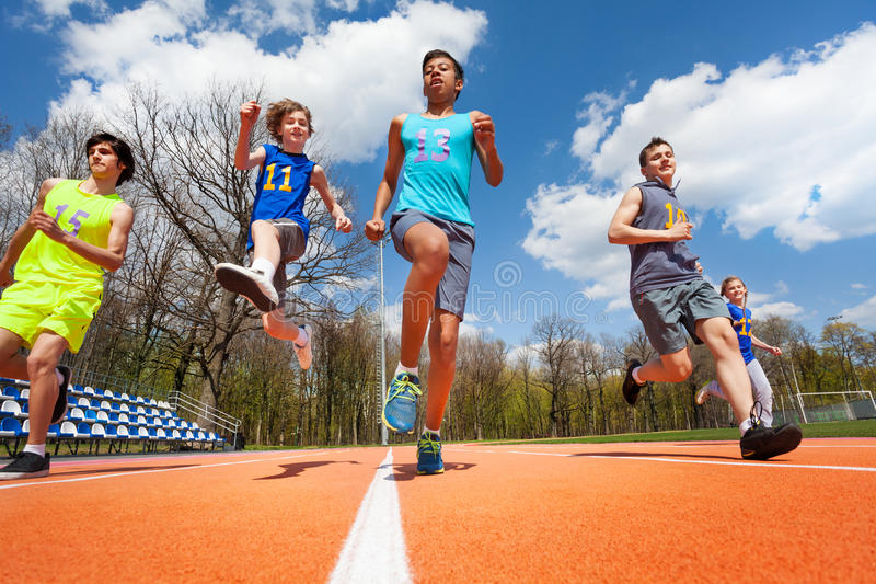 Athlètes adolescents ayant l'amusement sur le champ de courses photographie stock