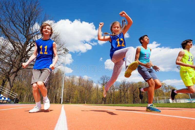 Athlètes adolescents heureux courant dans le stade images stock