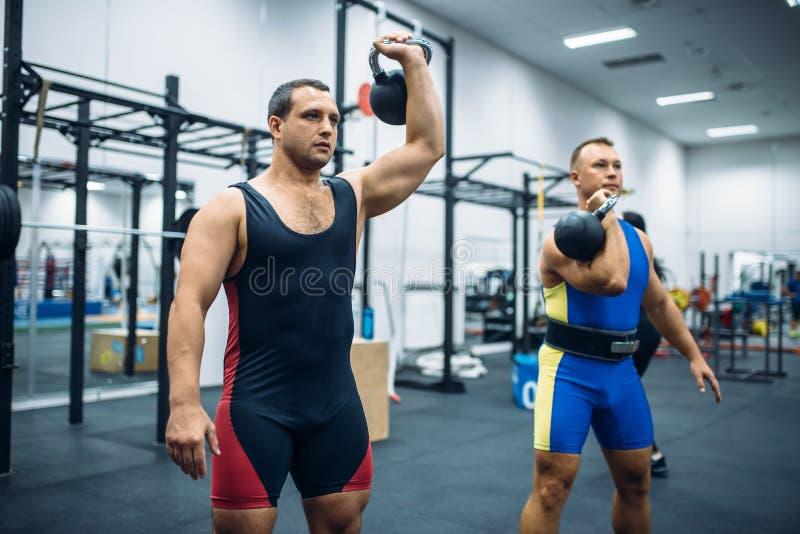 Athlètes avec des poids dans le gymnase, levage de kettlebell image libre de droits