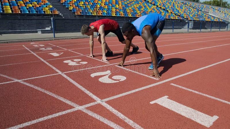 Athlètes multiraciaux en position de départ, prête à fonctionner après la commande, marathon images stock