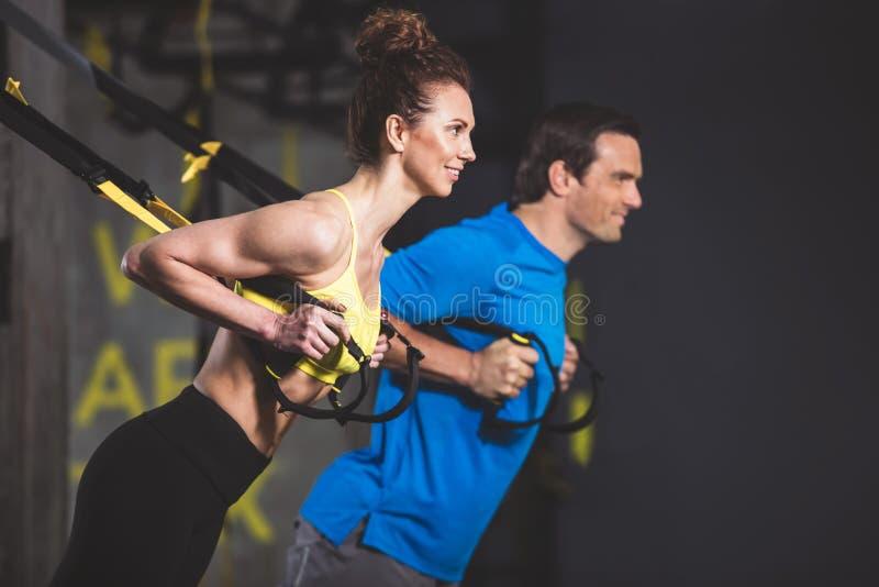 Athlètes positifs faisant la séance d'entraînement au centre de fitness photographie stock