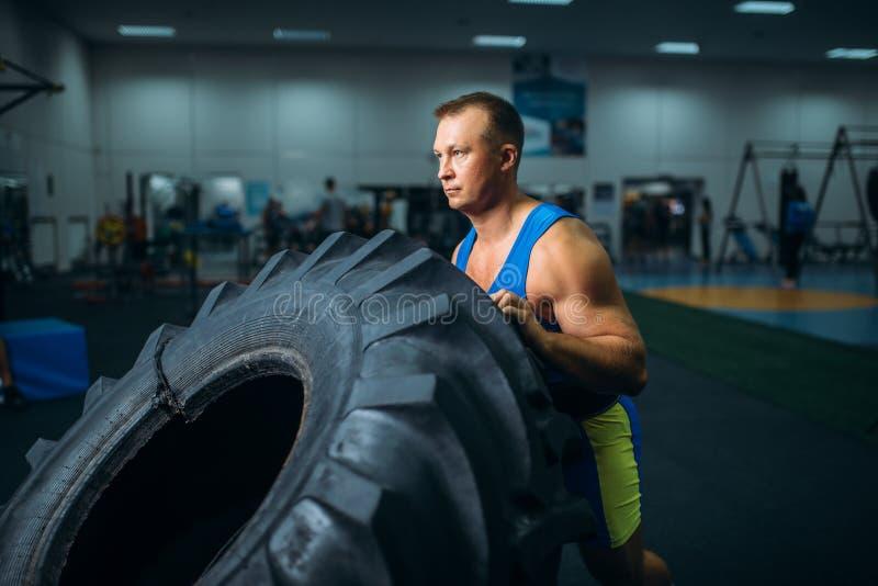 Athl?te faisant l'exercice avec le pneu de camion, crossfit image libre de droits