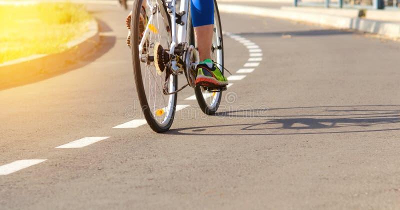 Athlet auf einem Fahrradweg bildet draußen auf einem Fahrrad aus, um Siege im Sport zu erzielen stockfotografie