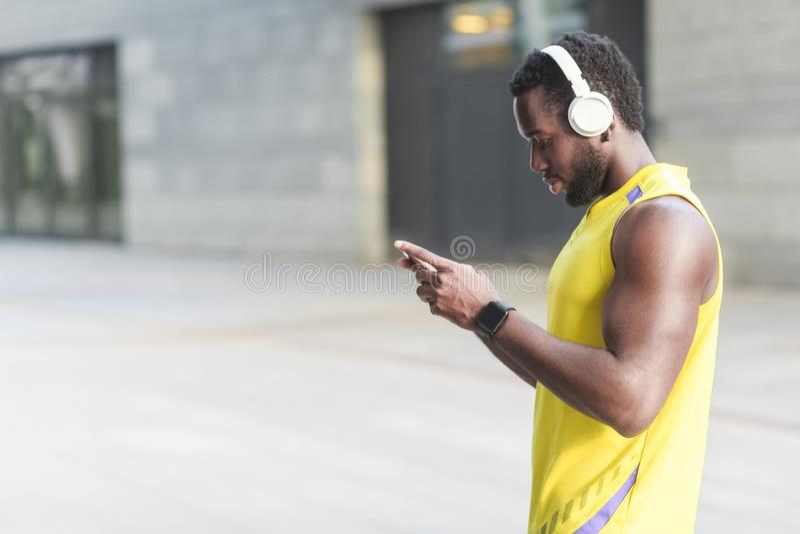 Athlet auf einem Morgenlauf Schaltet die Musik in der Titelliste lizenzfreie stockfotografie