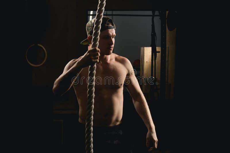 Athlet, der Eignungs-Seil-Aufstiegs-Übung im Eignungs-Turnhallen-Training tut stockfoto