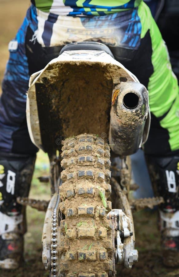 Athlet, der ein Sportmotorrad und ein schlammiges Rad auf ein laufendes Ereignis des Motocrosses reitet stockfoto