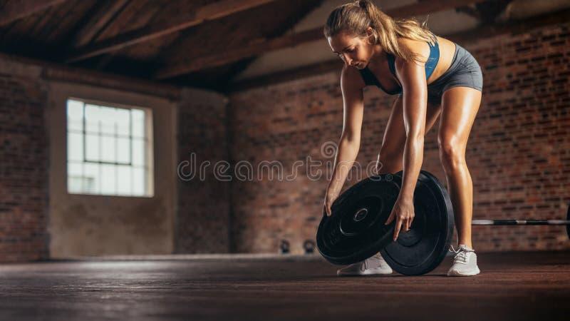 Athlet, der Gewichte für das Trainieren am Fitness-Club vorbereitet lizenzfreie stockbilder