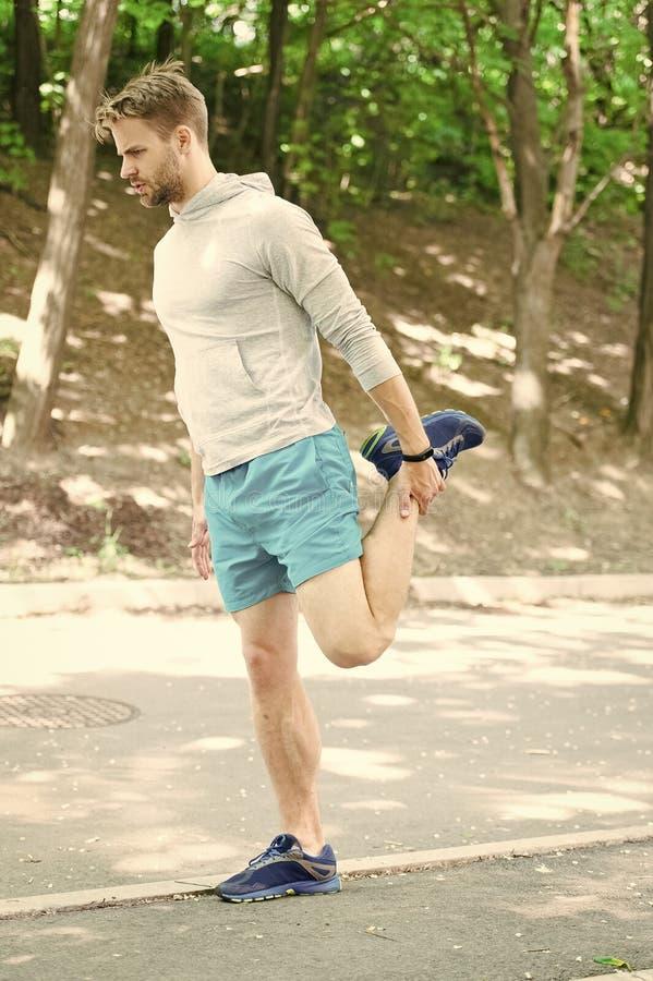 Athlet, der immer nach Training ausdehnt Sportler bereiten Training der Muskeln im Freien vor ?berzeugtes Gesicht des Mannl?ufers stockfotografie