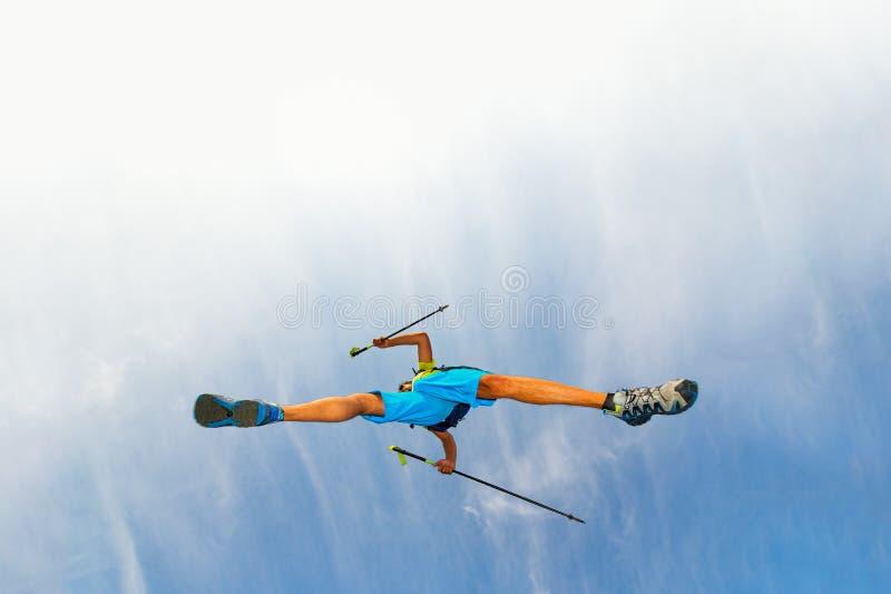 Athlet des jungen Mannes macht einen Sprung mit nordischen Spazierstöcken lizenzfreies stockfoto