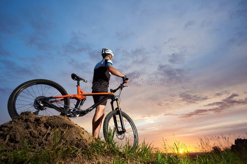 Athlet en el casco que coloca la bicicleta cercana y la presentación imágenes de archivo libres de regalías