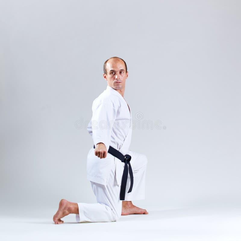 Athlet im weißen karategi bildet formale Karateübungen auf einem grauen Hintergrund aus lizenzfreies stockbild