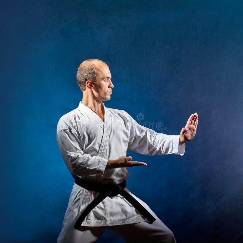 Athlet im weißen karategi bildet formale Karateübungen auf einem grauen Hintergrund aus lizenzfreie stockfotografie