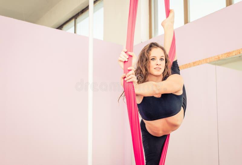 Athlet machend gymnastisch auf den Gummibändern lizenzfreie stockfotos