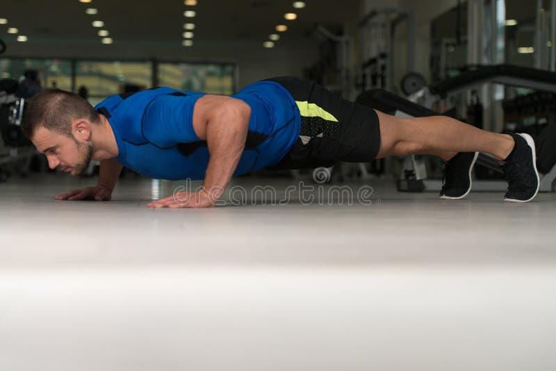Athlet Man Doing Push Ups auf Boden stockbilder