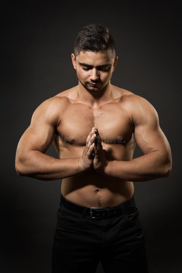 Athlet Man Studio Portrait, Sportler-nackter Körper, der mit den gefalteten Händen sich konzentriert stockfoto