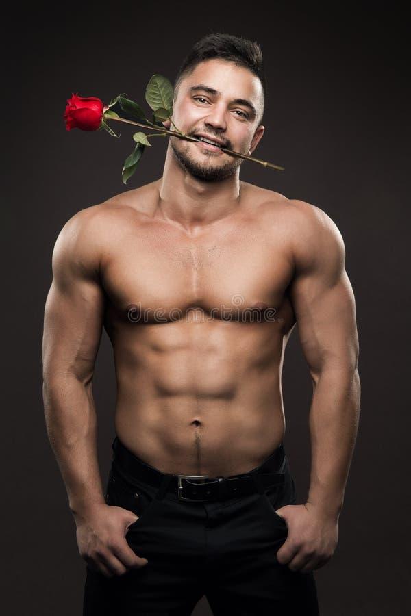 Athlet Man und Blume, athletischer Junge mit dem muskulösen nackten Körper, der Rose im Mund hält stockfotos