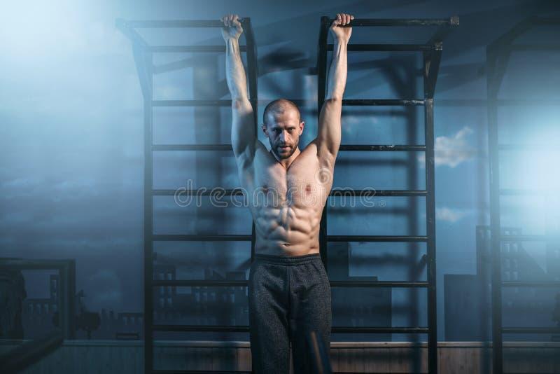 Athlet mit Training des muskulösen Körpers auf Stange stockfoto