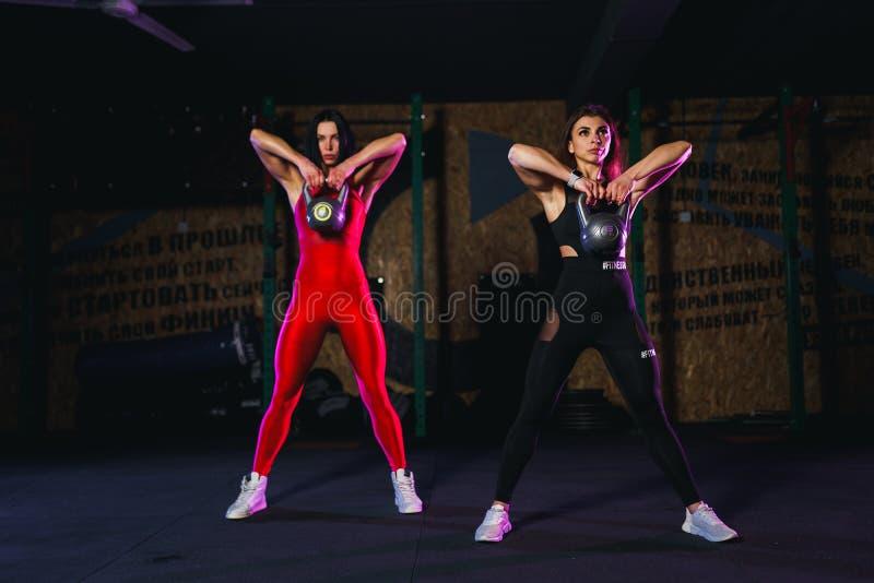 Athlet mit zwei attraktiver geeigneter Frauen, der ein Kesselglockenschwingen in der Turnhalle durchführt stockbild