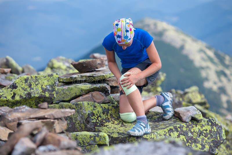 La fille fixe le bandage sur des genoux photographie stock