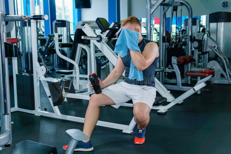 Athlet wischt seinen Schweiß zwischen Sätzen im Gewichtstraining ab lizenzfreies stockfoto