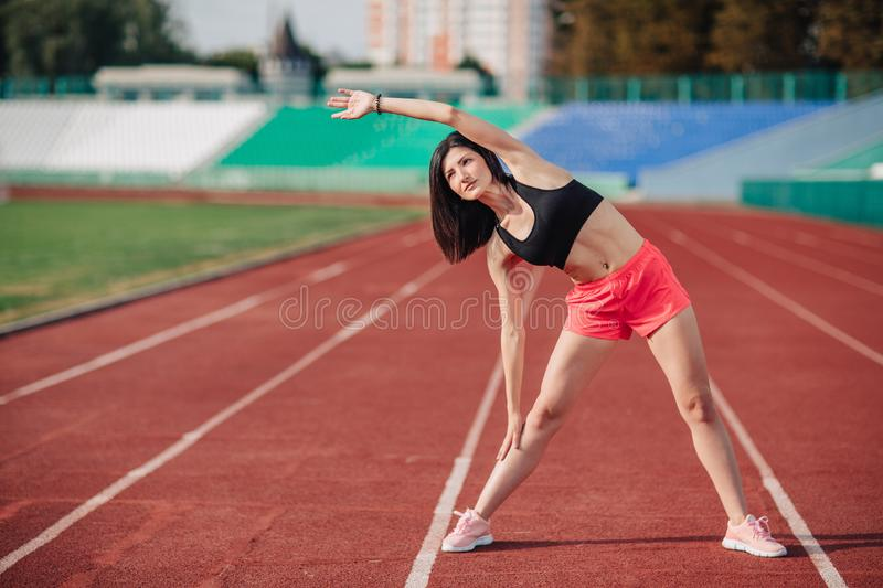 Athlete Attractive sporty brunette woman in pink shorts and top exercise stretching at sport stadium in evening, sunset. Sport and royalty free stock photo