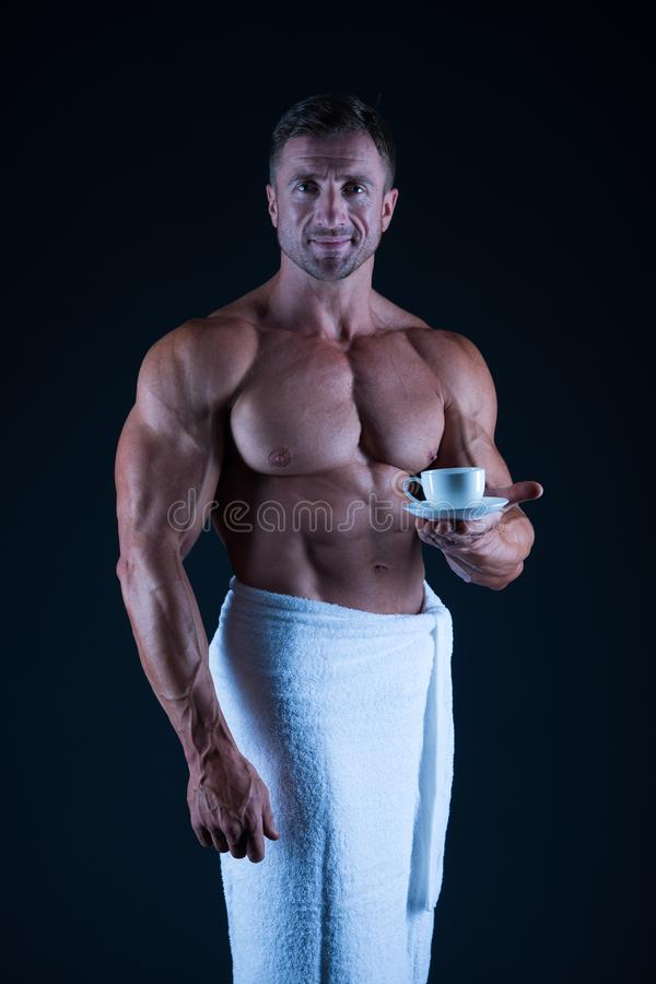 Athlete with bare torso. Sexy man in bath towel. muscular body man after shower. morning relax. morning coffee. Bodybuilding. Hygiene and health concept royalty free stock photography