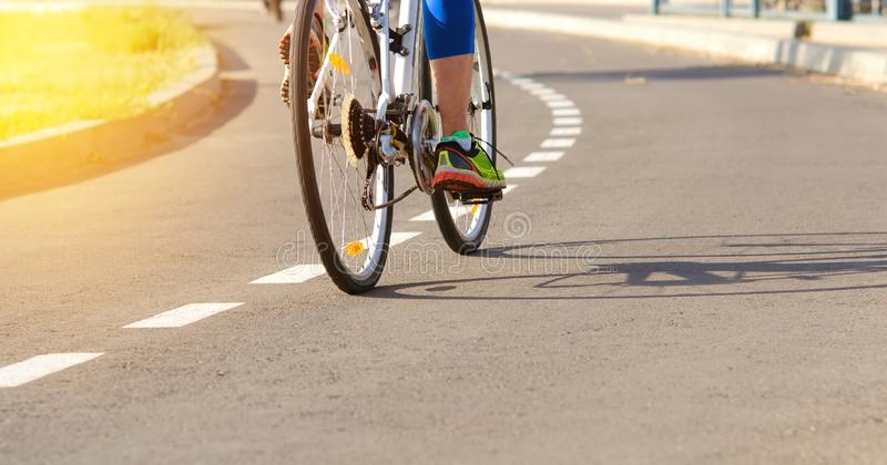 Athlete on a bike path trains outdoors on a bicycle to achieve victories in the sport. stock photography