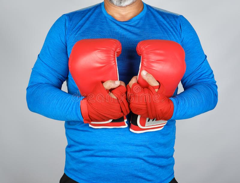 Athlete in blue clothes holding a pair of leather boxing gloves. Hands are rewound with red textile bandage stock photos