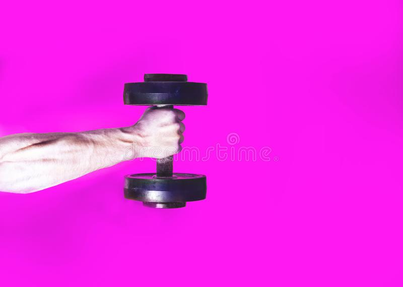Athlete bodybuilder, holding in hand a dumbbell, muscular hand on a pink background, your text there, flat, concept sports lifesty royalty free stock photo