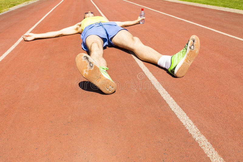 Athlete with broken green running shoes. An exhausted athlete on a running track wearing broken green running shoes with big holes in the sole stock photos