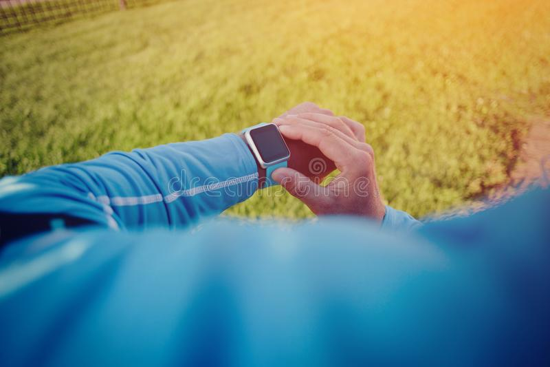 Athlete checking the program at his smart watch before training stock image