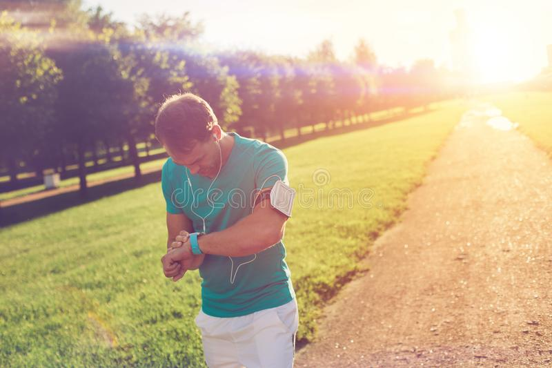 Athlete checking time results at his smart watches on the wrist after workout in the park stock images